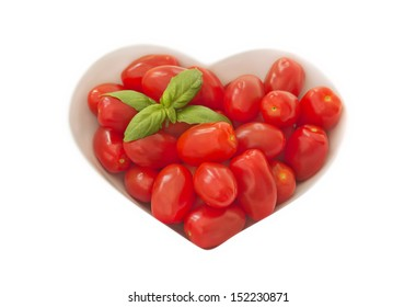 A bowl of baby plum tomatoes on a light coloured cloth. there is a sprig of basil in the top left hand corner to give a splash of green.