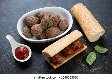 Bowl with baked beef meatballs and homemade sandwiches on a brown stone background, studio shot