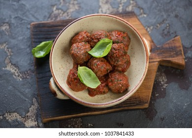 Bowl of baked beef meatballs in tomato sauce on a rustic wooden chopping board, elevated view on a brown stone background