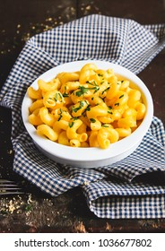Bowl of baked pumpkin macaroni and cheese served with fresh parsley on a wooden table, selective focus. Traditional american food. Comfort food. Pasta dish.