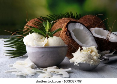 Bowl with balls of coconut ice cream and desiccated coconut on wooden table