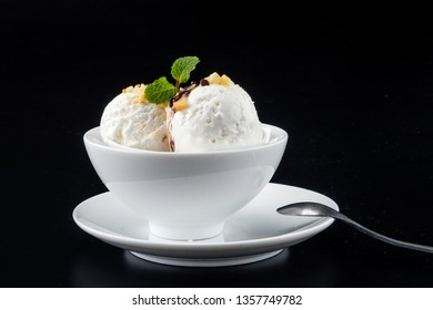 Bowl with balls of home made coconut ice cream, topping with walnut, chocolate, mint leaves on black background