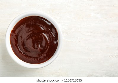 Bowl with barbecue sauce on white table