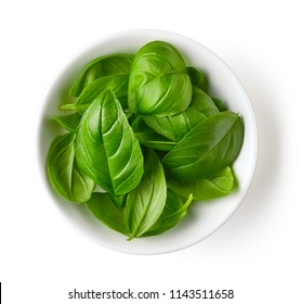 Bowl of basil leaves isolated on white background, top view
