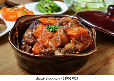 A bowl of beef stew on a wooden table
