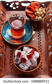 Bowl with berries turkish delight rahat lokum, turkish red tea, pistachios and dried apricots on wooden tray. Breakfast concept on white background, closeup view