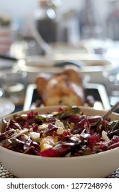 Bowl of bittersweet salad with oranrges, radicchio, ricotta cheese and pomegranate seeds. Table served for family and friends. Selective focus.