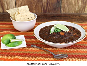 A bowl of black bean soup garnished with jalapeno pepper slices and fresh lime.