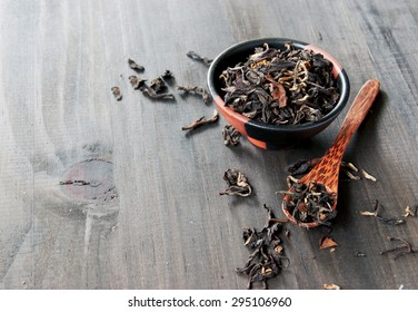 bowl with black tea and spoon on a wooden table