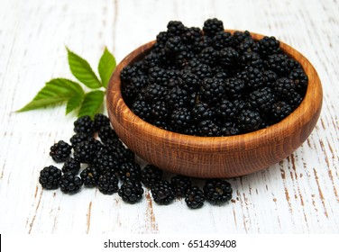 Bowl with Blackberries on a old wooden background