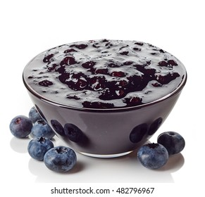 Bowl of blueberry jam isolated on white background