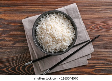 Bowl with boiled white rice and chopsticks on wooden table