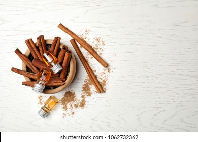 Bowl with bottles of cinnamon oil and sticks on wooden background