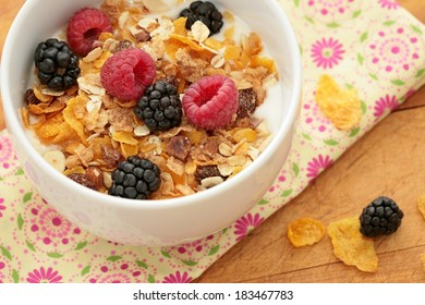 Bowl of breakfast healthy muesli and corn flakes with berries.