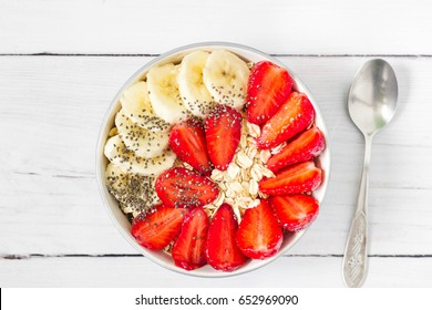 Bowl of breakfast muesli decorated with banana, strawberry slices and chia seed, top view.