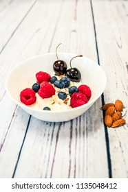 A bowl breakfast of skyr and fresh fruits of rasperry, blueberry, cherry and almonds