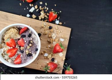 Bowl of breakfast weet-bix, muesli,granola  topped with strawberries, buckwheat, dried blueberries, and nut acai powder