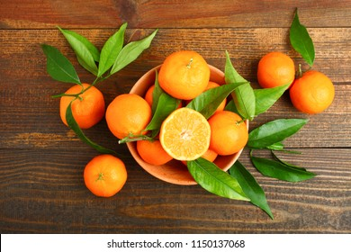 Bowl with bright and fresh tangerines on wooden background.