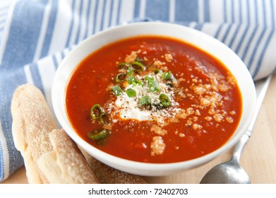 Bowl of Bright Red Creamy Tomato Soup with Yogurt, Cheese,Onions and Breadsticks