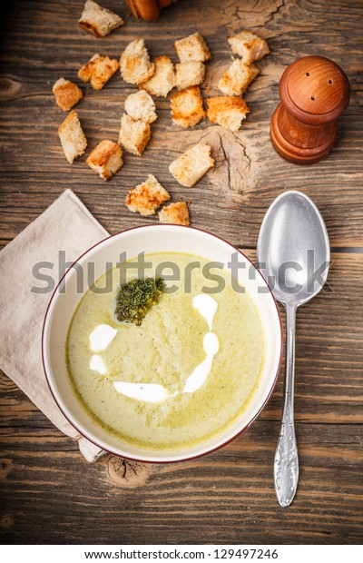 Bowl of broccoli soup with bread croutons, from above
