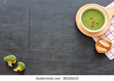 Bowl of broccoli soup and fresh bread on black background. Top view. Place for text.