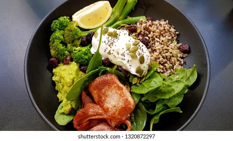 A bowl of brown rice, quinoa, broccolini, spinach, avocado, spinach, poached eggs, and bacon.