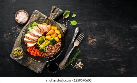 Чаша Будды. Гречка, тыква, куриное филе, авокадо, морковь. На черном фоне. Вид сверху. Свободное место для текста.