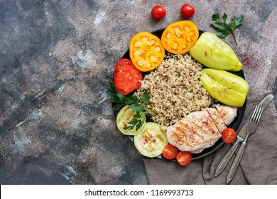 Bowl of buddha, chicken grilled, kinoa, tomato, sweet pepper and zucchini on rustic background, top view.Delicious balanced food concept