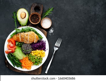 Bowl Buddha.Quinoa, chicken breast, arugula, avocado, red cabbage, carrot, green  peas, corn, tomato, green beans in a white plate on a stone background. with copy space for your text