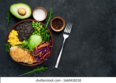 Bowl Buddha.Quinoa, chicken breast, avocado, red cabbage, arugula, carrot, green  peas, corn, broccoli, green beans in a plate on a stone background, with copy space for your text