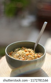 Bowl of bulgur wheat, roasted pumpkin, feta cheese and parsley salad. Selective focus, intentional lens flare.