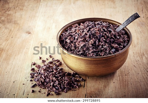 Bowl of cacao nibs on wooden background