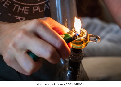 A bowl of cannabis leaf being burned and smoked out of a bong. Up close on the flame.