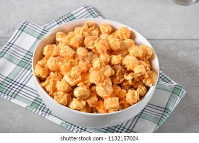 A bowl of caramel cheddar cheese popcorn from a high angle view.