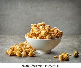 bowl of caramel popcorn on grey table