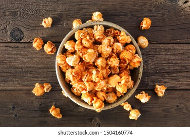 Bowl of caramel popcorn with scattered kernels. Top view over a rustic wood background.