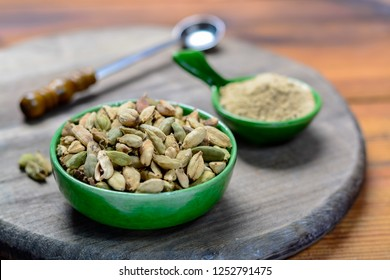 Bowl with cardamom pots and cardamom powder, used for cooking and traditional medicine close-up, spices collection