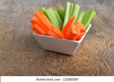Bowl of carrot and celery sticks on wooden background