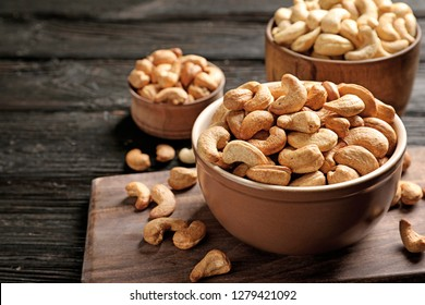 Bowl with cashew nuts on wooden table. Space for text