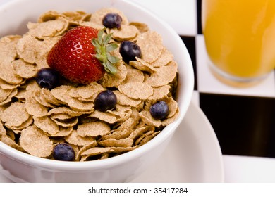 Bowl of cereal with fresh fruit and a glass of juice.