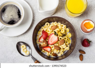 Bowl with cereal rings cheerios, strawberries and milk. Fresh coffee, orange juice and egg. Balanced breakfast concept.