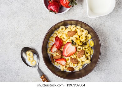 Bowl with cereal rings cheerios, strawberries and milk. Traditional breakfast concept.