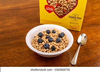 A Bowl of Cheerios with Blueberries on a Wood Table with box in background