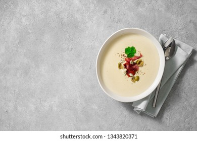 Bowl of cheese soup with bacon and olives top view copy space