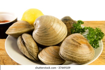 Bowl of cherrystones (quahogs, or hard-shell clams) with lemon, parsley and cocktail sauce on old cutting board