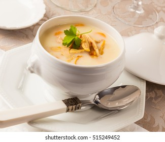 A bowl of chicken cream soup on a dinner table.