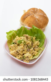 A bowl of chicken salad in a bowl with bun in the background.