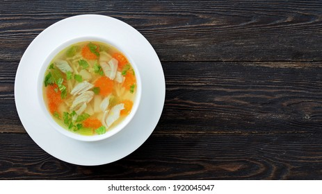 Bowl of chicken soup on a brown wooden table with copy space. Top view.