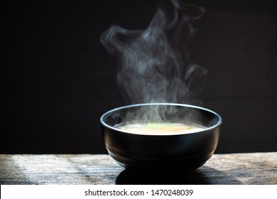 Bowl of chicken soup. steam of hot soup with smoke wood bowl on dark background.selective focus,hot food concept