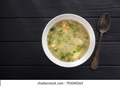 Bowl of chicken soup. Chicken soup in a white plate on a black wooden table. Free space for text. View from above. Top view.